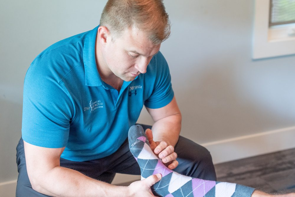 Chiropractor assessing foot injury from running